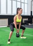 Side view portrait of an athlete woman doing exercises lifting kettlebell in gym working out back, legs muscles. stock image