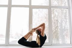 Side view portrait of attractive young blonde woman working out in fitness club or at home, doing yoga or pilates exercise. Dhanur. Asana, Bow pose. Full length royalty free stock photos