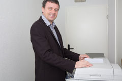 Side view portrait of business man using photocopy machine in office. Side view portrait of businessman using photocopy machine in office Stock Photography