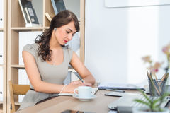 Side view portrait of a businesswoman sitting concentrated, writing, organizing her timetable in light office. Stock Photo