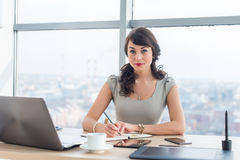 Side view portrait of a businesswoman sitting concentrated, writing, organizing her timetable in light office. Royalty Free Stock Photos