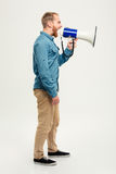 Side view portrait of a casual man screaming in megaphone Stock Images