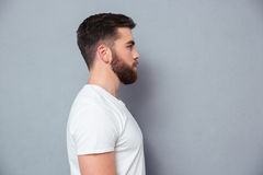 Side view portrait of a casual man. Standing over gray background Stock Image
