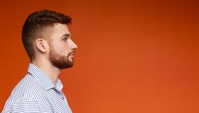 Side view portrait of concentrated young man on red. Side view portrait of concentrated young man looking away at copy space on orange background, panorama, free royalty free stock image