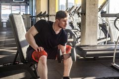 Side view portrait of concentration young adult man handsome athlete working out in gym, sitting on a bench and holding one. Dumbbell with raised arm, doing royalty free stock photo