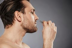 Side view portrait of a confident man removing nose hair. With tweezers isolated over gray background Royalty Free Stock Photos