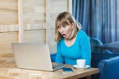 Side view portrait of emotional shocked young businesswoman in blue t-shirt are sitting in cafe, reading news and remotely working. Don`t believe! Side view royalty free stock image
