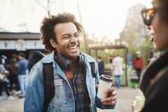 Side-view portrait of fashionable cute african-american guy with afro hairstyle laughing out loud over joke while. Talking with friend in park, drinking coffee Stock Photos