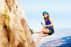 Female climber using abseil method of roping down. Side view portrait of female climber using technique of the abseil method of roping down Stock Images