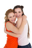 Side view portrait of a female embracing her friend Stock Photo