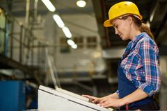 Young Woman Operating Machine Units at Factory stock image