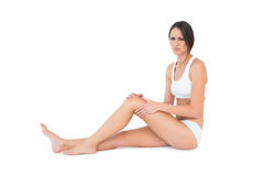Side view portrait of a fit woman with knee pain Royalty Free Stock Photography