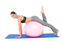 Side view portrait of a fit woman stretching on fitness ball Royalty Free Stock Photos