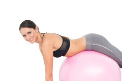 Side view portrait of a fit woman stretching on fitness ball Royalty Free Stock Image