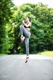 Side view portrait of a fitness woman jumping sport exercises outdoors in the park stock photo