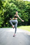 Side view portrait of a fitness woman jumping sport exercises outdoors in the park royalty free stock photography