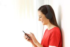 Profile of a girl listening to music on line on white. Side view portrait of a girl listening to music on line with a smart phone and headphones isolated on Stock Images