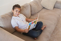 Side view portrait of a girl reading storybook on sofa Stock Photo