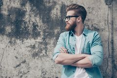 Side view portrait of handsome brutal bearded guy dressed in cas. Ual clothes standing with crossed arms against concrete wall Royalty Free Stock Photo
