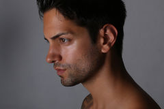Side view portrait of an handsome man with nude torso. Over gray background Stock Photography