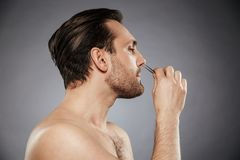 Side view portrait of a handsome man removing nose hair. With tweezers isolated over gray background Stock Photo