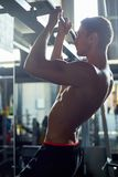 Muscular Man Pulling Up on Bar in Gym royalty free stock photo