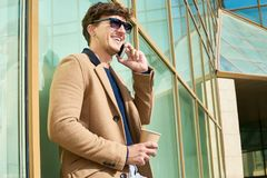 Handsome Man Speaking by Phone Outdoors. Side view portrait of handsome young man wearing sunglasses speaking by phone while enjoying coffee break outdoors in stock photo
