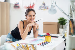 Side view portrait of a happy artist at the workplace. Young woman with paintbrush Royalty Free Stock Photo