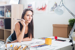 Side view portrait of a happy artist at the workplace. Young woman with paintbrush stock photography
