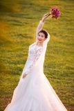 Side view portrait of happy bride holding flower bouquet on grassy field.  Stock Photo
