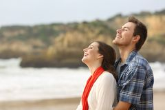 Happy couple breathing fresh air together on the beach. Side view portrait of a happy couple breathing fresh air together on the beach Royalty Free Stock Photos