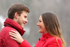 Happy couple in love looking each other in winter stock image
