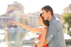 Couple pointing away in the street. Side view portrait of a happy couple pointing away in the street on summer vacation royalty free stock images