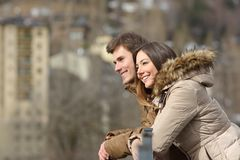 Couple sightseeing outdoors in the street in winter. Side view portrait of a happy couple sightseeing outdoors in the street in winter royalty free stock image