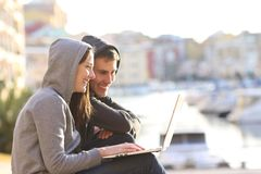 Couple of teens using a laptop on vacation. Side view portrait of a happy couple of teens using a laptop on vacation Stock Photos