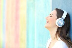 Happy girl listening to music on a colorful wall stock images