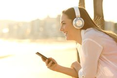 Happy girl listening to music contemplating the beach. Side view portrait of a happy girl listening to music contemplating the beach at sunset royalty free stock images