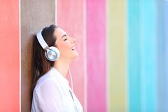 Happy girl relaxing listening to music in a colorful wall stock photography