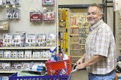 Side view portrait of a happy mature man with shopping cart in hardware store Royalty Free Stock Photo