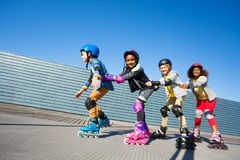 Cute kids rollerblading one after another outdoors. Side view portrait of happy multiethnic kids rollerblading one after another on the track of stadium stock image