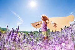 Little dreamer preparing to fly like a bird. Side view portrait of happy preteen girl wearing homemade wings, playing outdoors in summer Stock Images
