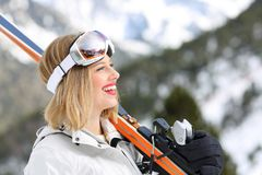 Happy skier holding skis looking at mountain. Side view portrait of a happy skier holding skis looking in a snowy mountain on winter holidays Stock Photo