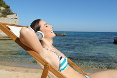 Happy tourist listening to music resting on the beach royalty free stock photos