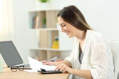 Happy woman doing domestic accounting. Side view portrait of a happy woman doing domestic accounting at home Stock Photography