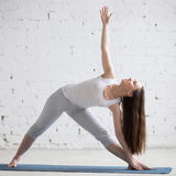 Side view portrait of happy woman doing Extended Triangle pose. Attractive cheerful young woman working out indoors. Beautiful model doing exercises on blue mat stock photos