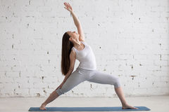Side view portrait of happy woman doing Reverse Warrior Pose Stock Photos