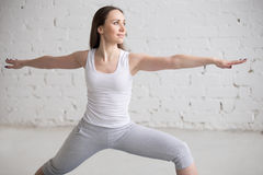 Side view portrait of happy woman doing Virabhadrasana II Pose Stock Image