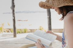 Side view portrait of a happy woman reading a book on the beach in summer vacation royalty free stock photo