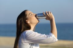 Woman refreshing drinking soda on the beach. Side view portrait of a happy woman refreshing drinking soda sitting on a bench on the beach Royalty Free Stock Photography
