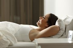 Woman relaxing sleeping at home in the night. Side view portrait of a happy woman relaxing sleeping on a bed at home in the night stock photography
